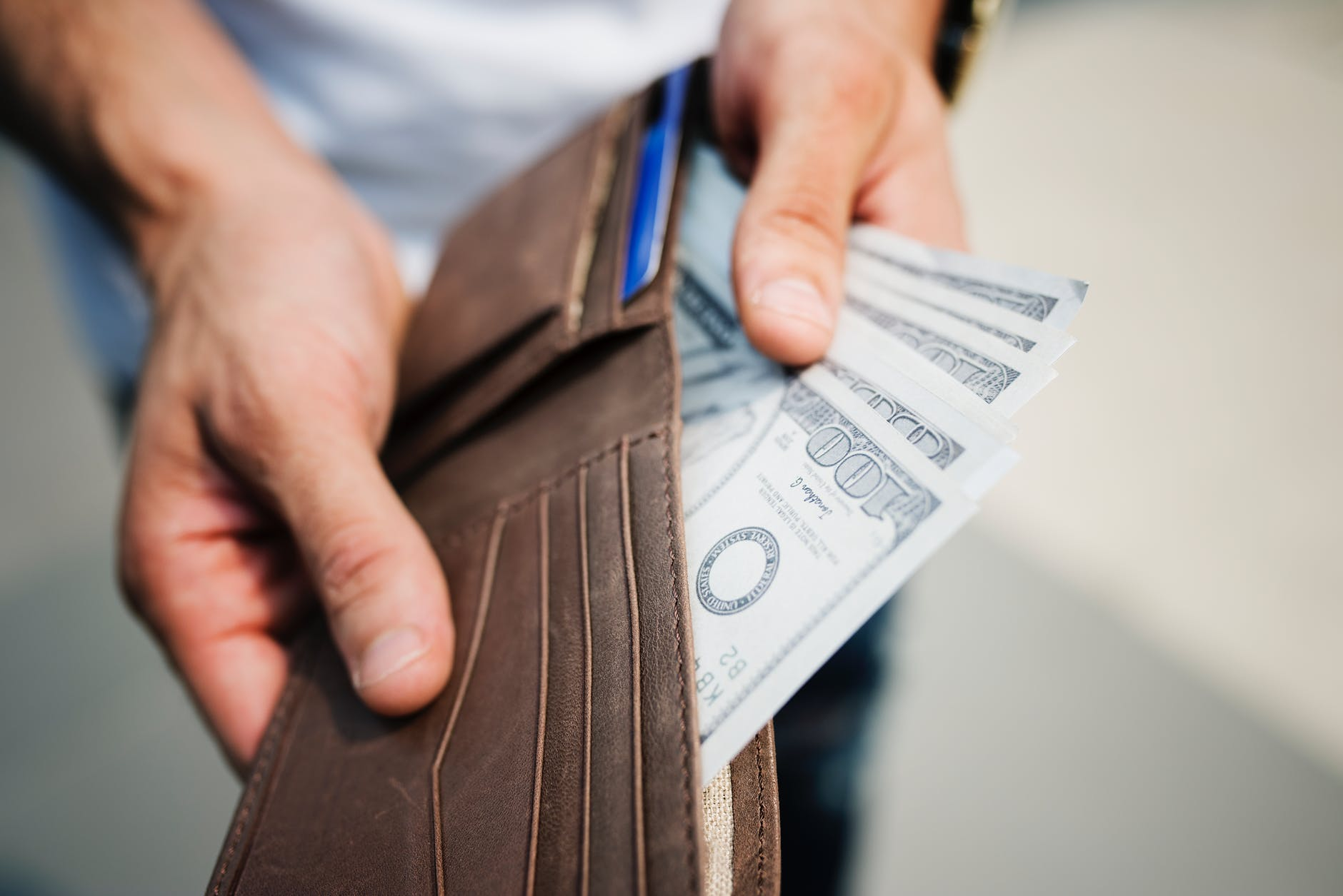 man holding brown leather bi fold wallet with money in it - 4 Types of Baseball Bets - Learn Them All