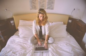woman working bed laptop typing 300x198 - woman-working-bed-laptop-typing